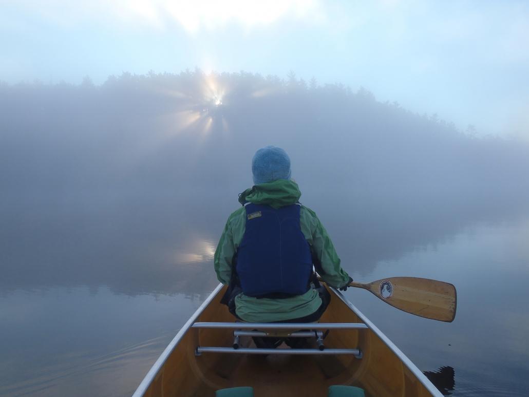 Man padlding in canoe in a morning fog