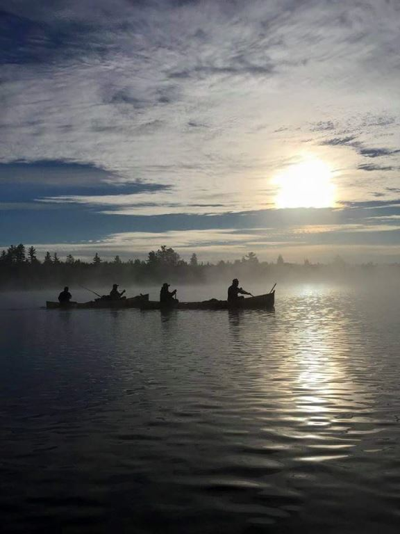 People canoeing as the sun rises